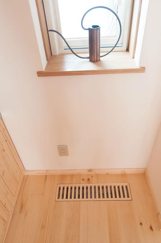 換気システムを起動させると、この「ガラリ」を通して地中から新鮮な空気を取り込み、冬には床下に二階の暖気を送り込みます。窓枠の奥行が深いことにお気づきですか。これは200㎜断熱材の厚さです。この断熱材は「木の繊維」社の「ウッドファイバー」というものです。エコアパートの断熱機能を大きく高めています。