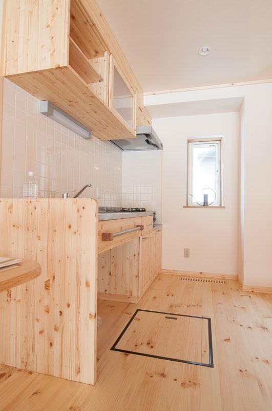 キッチン台上部の収納棚も職人手作り。棚の下に照明が付いています。キッチンの天井にもLEDのダウンライトが埋め込まれていて、キッチン全体を明るく照らします。