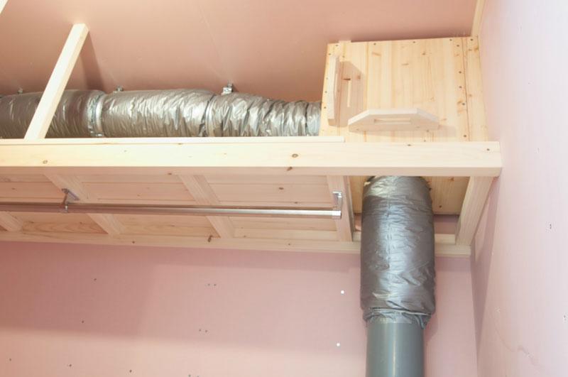 クローゼット内の上部に設置されている「換気システム」。 横に伸びている筒の先端は屋外に出ていて冬は湿気を含んだ空気を排気し、夏は室内にとどまっている熱気を排気します。縦に下に伸びている筒は床下につながっています。冬は湿気を除いた暖気を床下へ送り込み、アースチューブで取り込んだ新鮮な空気と混ざり合いキッチンのガラリを通して一階に上がっていきます。一階ではペレットストーブの熱と合流し、スノコを通してまた二階へ上がっていきます。この循環が高性能な換気システムをつくり上げています。 システムの詳細は入居時に改めてご説明いたします。結露知らずの快適生活が送れます。