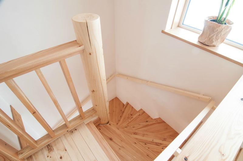 らせん階段を支えるトドマツの丸い柱。もちろん塗料は二度塗り仕上げで、白い木肌はやさしい手触りです。ひび割れが入っていますが、無垢材にとっては自然の成り行きですのでご心配なく。構造物のあちこちの部材にひび割れが発生しますが、構造物の強度にはまったく問題はありません。新築一年目は、部材の割れる音が屋内に響くそうです。家も生きているという証のようなものですので、驚かないでください。